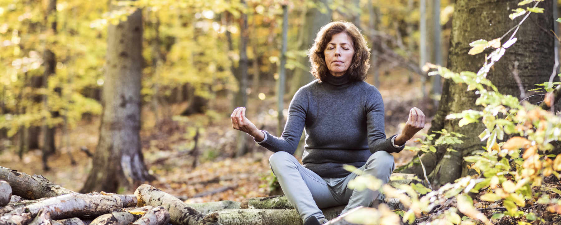 Image of a senior woman meditating in an autumn forest as content for wise living over 50s wellbeing guides - from improving memory to dealing with sleep problems