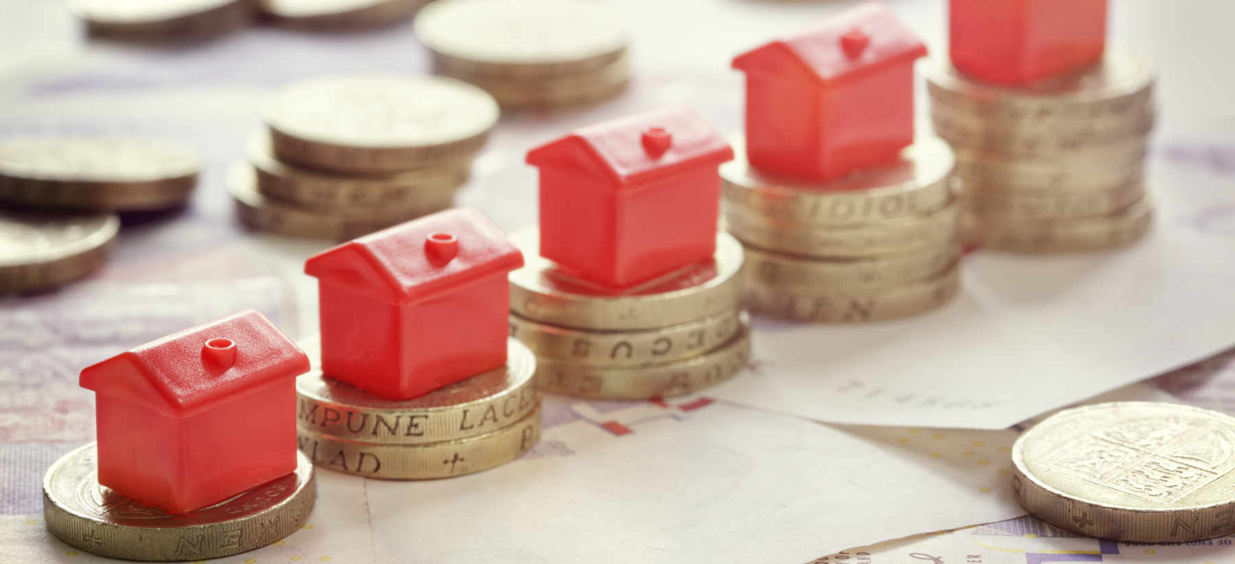 Image of Monopoly houses on pound coins as concept for wise living over 50s money and property legal guides - from making a will to dealing with contentious probate