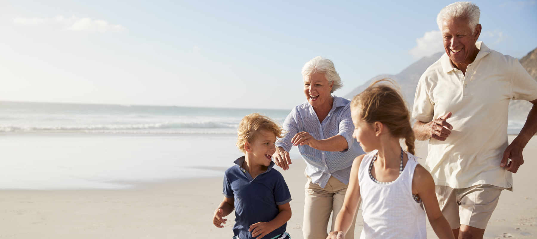 Image of grandparents and grandchildren on a beach as concept for over 50s insurance - including travel insurance, home insurance and cat insurance - with wise living over 50s insurance guides