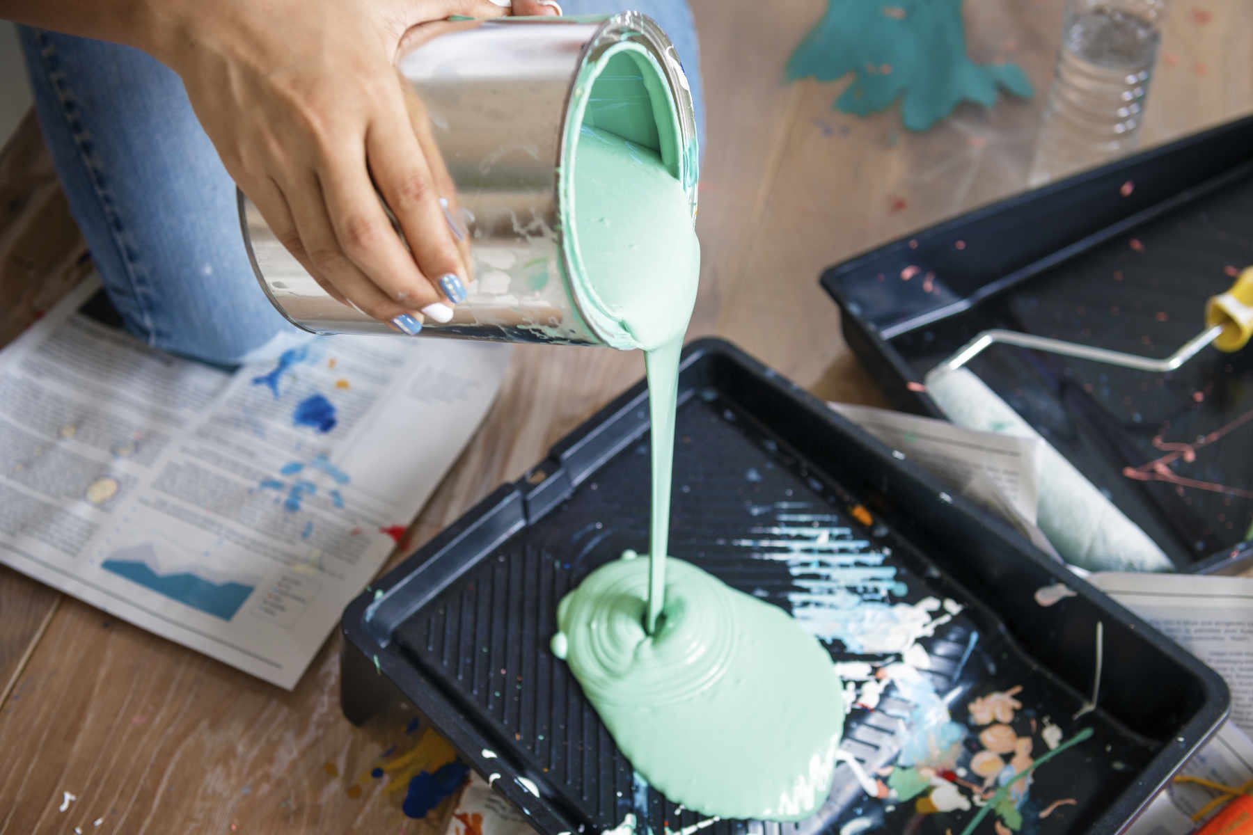 Image of woman pouring green paint as concept for wise living over 50s property guides - from home improvements to buying and selling property