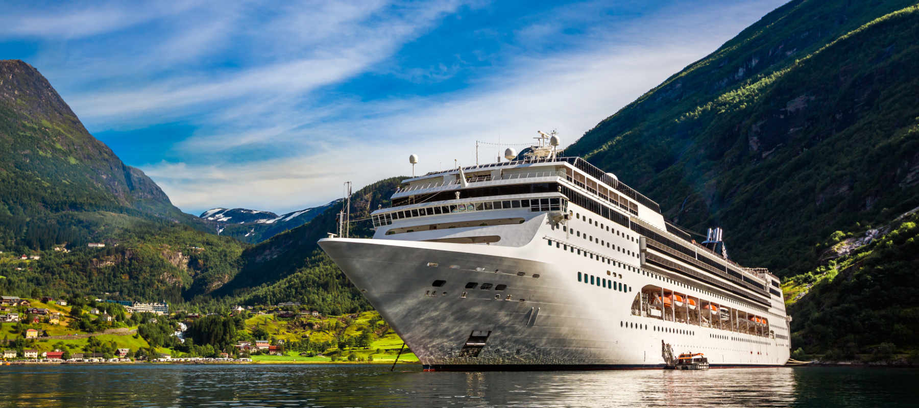 Image of a cruise liner on a fjord as concept for wise living over 50s cruising guides - from Mediterranean cruises to getting cheap cruise deals
