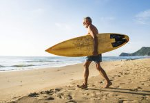 Image of a senior man with surfboard on a beach taking solo holidays
