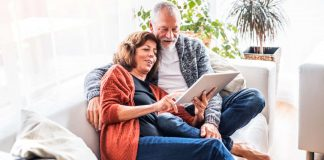 Image of a senior couple sitting on a sofa researching retirement homes