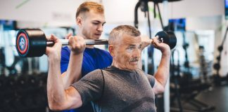 Image of a senior man lifting weights with help after he needed to find a personal trainer