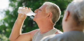 Image of seniors drinking water from a bottle in a park in summer to stop heat stroke
