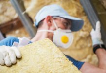 Image of a man installing loft insulation wearing a mask and hat using gloved hands to handled mineral rock wool insulation