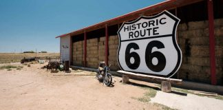 Image of a motorbike by the Route 66 sign as part of a Route 66 tours planning guide