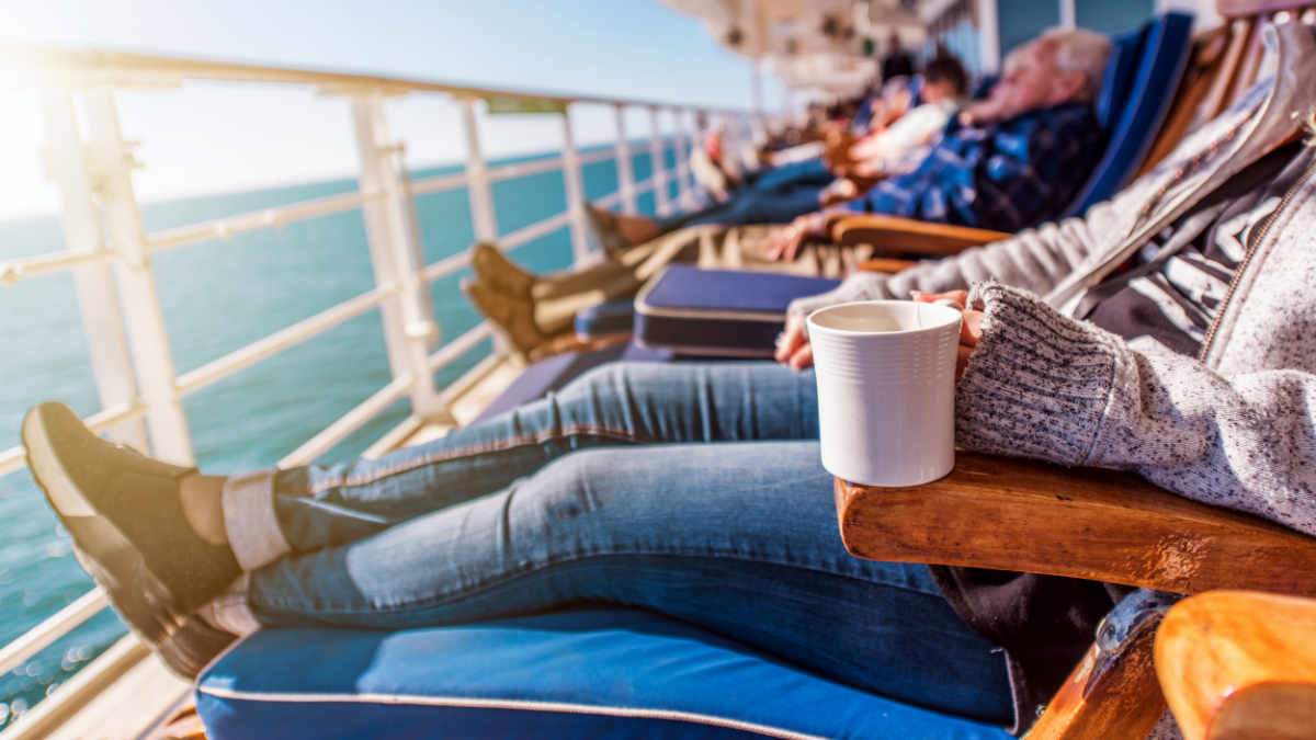 Image of a senior woman relaxing on the deck of a ship as part of a single cruises holiday
