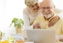 Image of a happy senior couple using a laptop to go online thanks to installing a wifi signal booster to extend wifi range