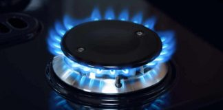 Image of a gas flame on a black cooker hob for energy saving tips concept that can help reduce your fuel bill