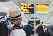 Woman backpacker looking at airport delays board considering flight delays compensation