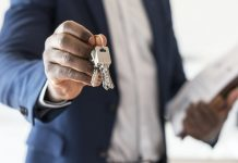 Image showing a man in a suit holding out house keys as a concept image for choosing the best estate agents