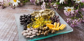 Image of a collection of menopause supplements on a glass dish surrounded by flowers
