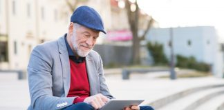 Image of a senior man in city with phone and laptop sitting outside using public wifi