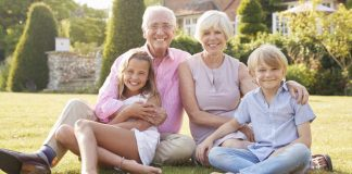 Image of grandparents and grandchild sitting outside in the sun thinking about saving for grandchildren