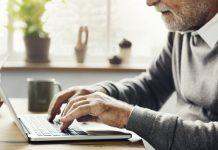 Senior man on laptop ensuring social media safety when online