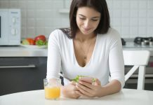 Image of a woman sitting in a kitchen using a smartphone to record drinking an orange juice into her diet apps