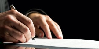 Human hand signing a probate form for article on what is probate