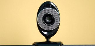 Image of a wifi security camera shown balancing on top of a monitor