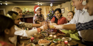 A happy family toast and celebrate at Christmas dinner having managed to beat Christmas stress