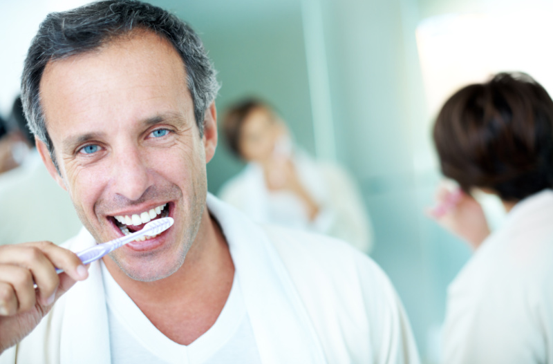 Boost your brainpower - Mature man brushing his teeth with his partner in the background.