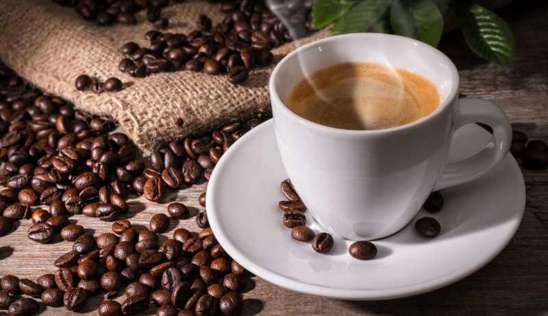 Brain food – Cup of coffee and coffee beans on wooden background.