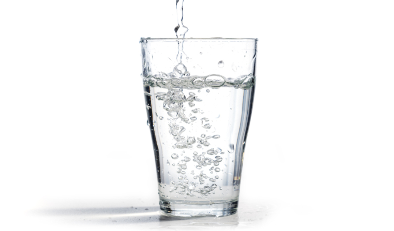Brain food - water is poured into a drinking glass, isolated on a white background with copy space