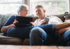 Senior couple on a sofa using a tablet and phone for an ISA transfer