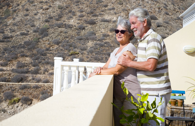 Senior couple retired to Spain standing on the terrace outdoor with mountains background.