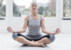 Senior woman sitting cross legged meditating ti improve concentration at home