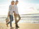 Mature couple on beach to illustrate how much do I need to retire?