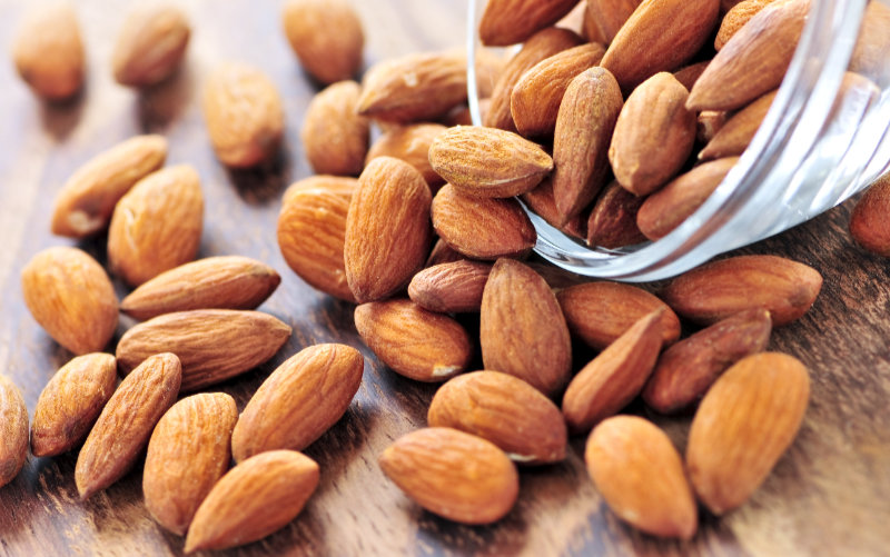 Raw almonds spilling out of small glass bowl – ideal as an insomnia cure