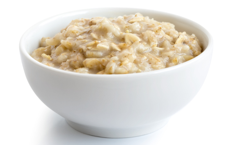 Prebiotic foods – Cooked whole porridge oats in white ceramic bowl isolated on white.