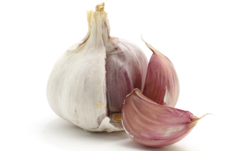 prebiotic foods - A garlic bulb with two cloves split off, isolated on a white background