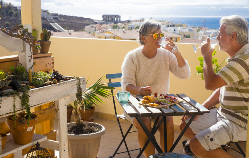 Retired couple on the rooftop terrace in Spanish home eating and drinking some food and drink.