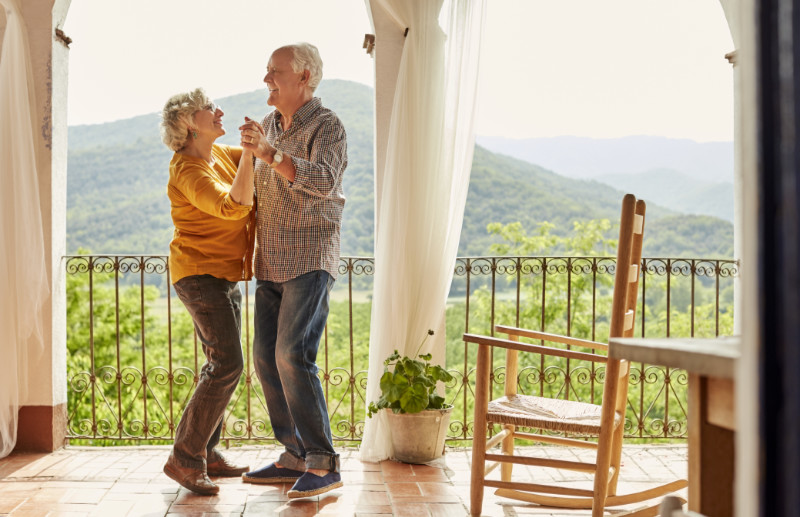 Happy couple dancing on a balcony in their Spanish home