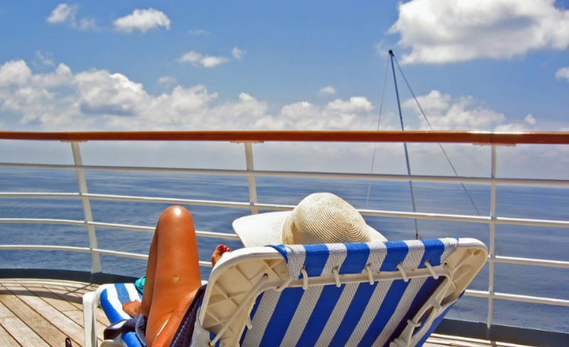 Solo cruise tips – a woman sits on a lounge chair and overlooks the ocean from a cruise ship