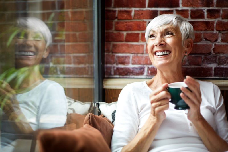 Senior woman having a nostalgic moment while drinking coffee a hot drink from a cup