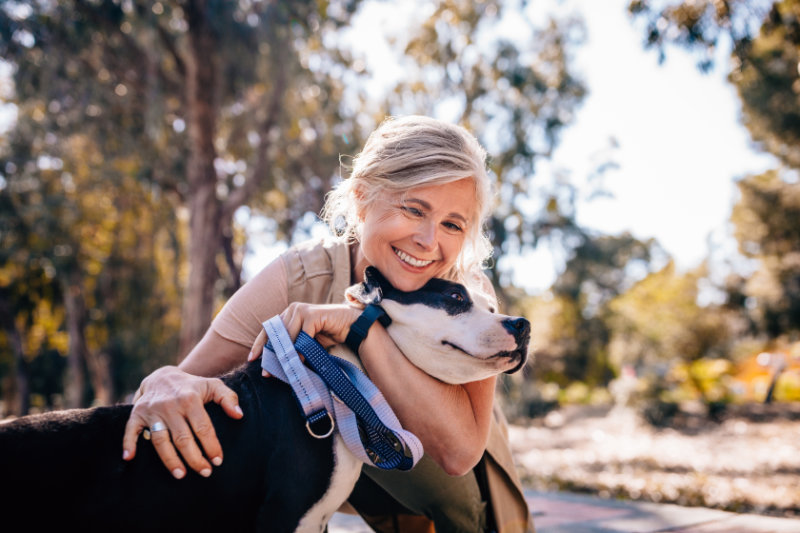 Affectionate mature woman embracing pet dog on walk to live well for longer