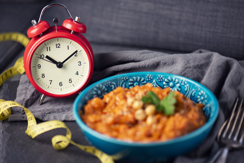 Losing weight with intermittent fasting illustrated with a clock and traditional, vegan Chana Alu Masala, an indian dish