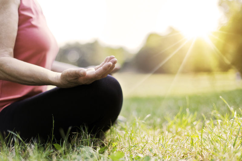 Senior woman meditating and doing yoga in park in a bid to live well for longer
