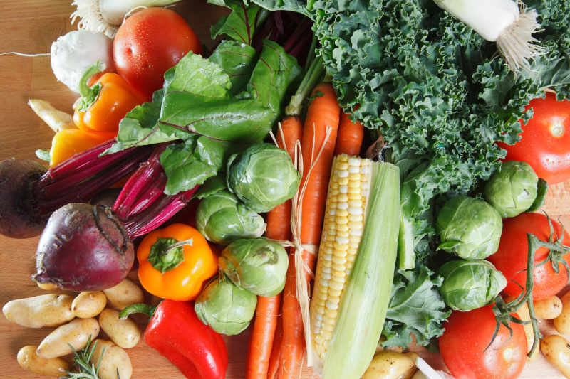 Group of colourful assortment raw vegetables including peppers, corn and kale