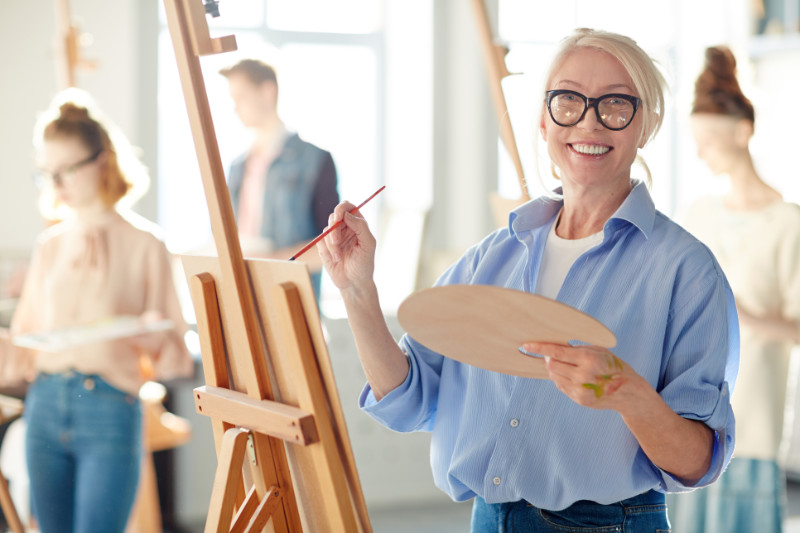 Woman looking at camera while painting with oil colours