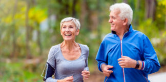 Exercise in autumn and winter: Smiling mature couple jogging in the park