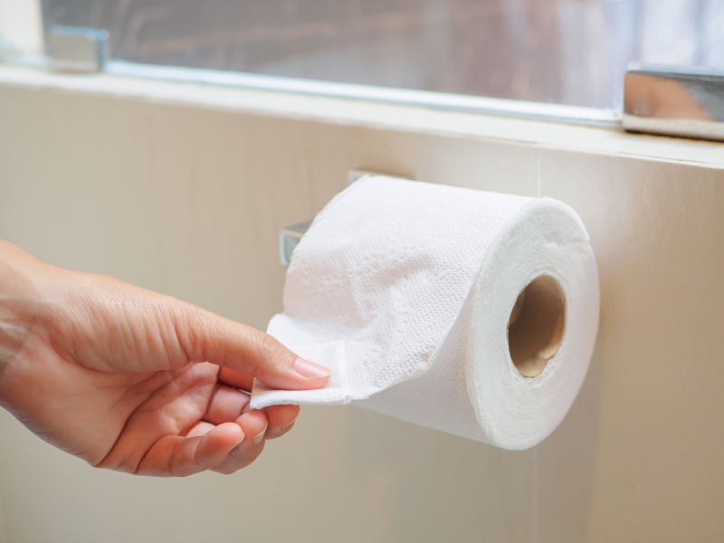 Mens Health issues Closeup hand picking a white tissue from tissue roll in the restroom.