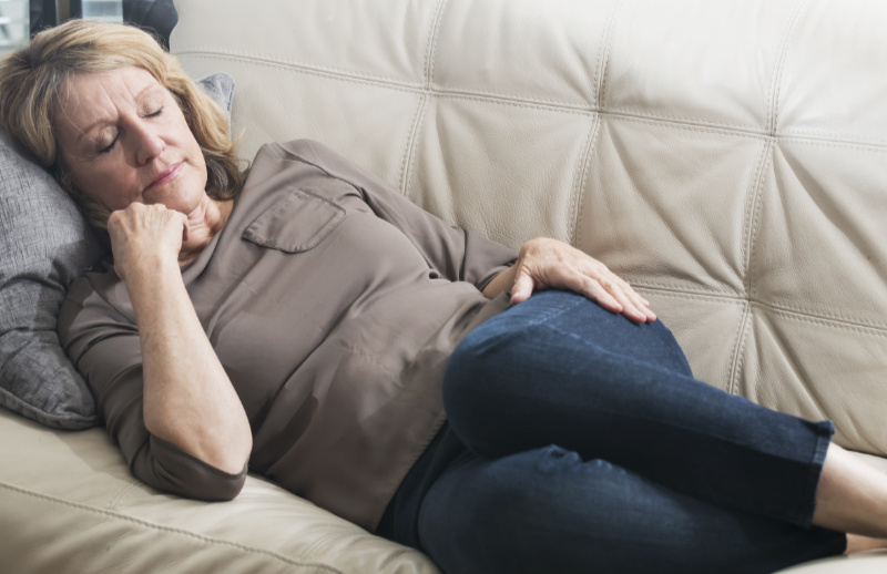 A senior woman at home on her couch, taking a power nap during the day.