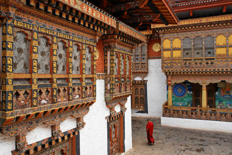 A monk walks among ornate carvings in a Punakha Temple
