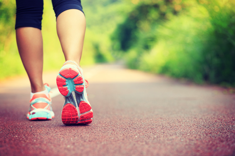 Benefits of walking Young fitness female runner legs ready for run on forest trail