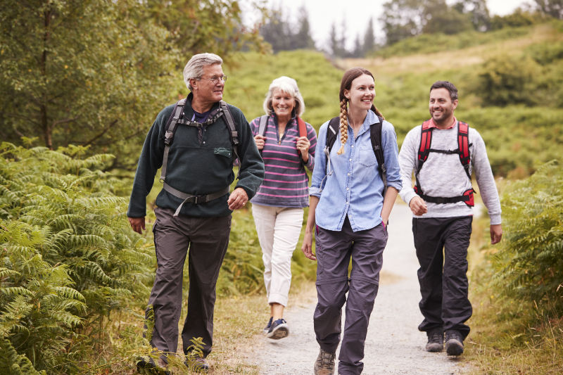 Benefits of walking Two mixed age couples walking on a countryside path during family camping adventure, front view