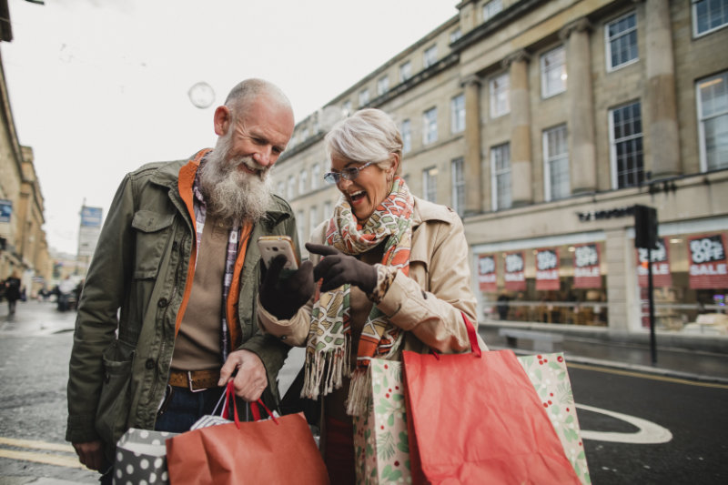 Guide to Black Friday shopping with senior couple on high street with bags